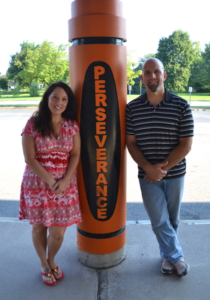 """Photo by Tom Rivers Kelly and Jay Kovaleski, both Albion teachers, are running a new program to help people focus on goals and find their passion in life. They are pictured by the """"Perseverance"""" crayon in front of the elementary school."""