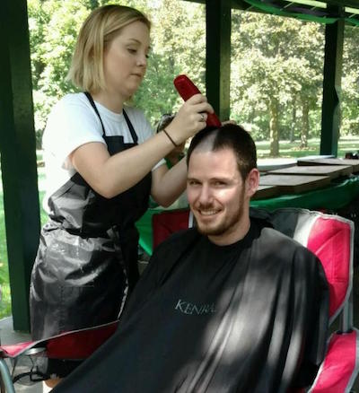 Provided photos: Gretta Smith, one of the volunteers who cut hair, buzzes Jesse Dole's hair this afternoon.