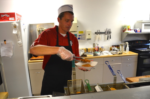 Dan Courtney, the assistant principal and athletic director at Holley, serves up an order of fries.