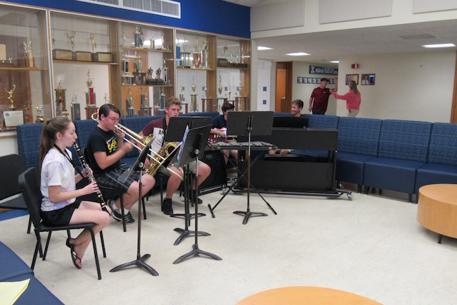 Kendall Jr./Sr. High vocal and instrumental music students provided entertainment during the Open House.  They are seated on new furniture in  the Commons area of the school.