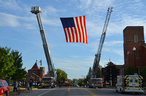 File photos by Tom Rivers: The ladder trucks from the Albion and Medina fire departments hold up a giant American flag during a Sept. 11 memorial service last year in Albion.