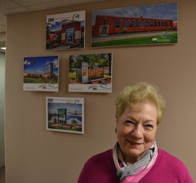 Gabrielle Barone is pictured at the Orleans EDA suite at 121 North Main St. in Albion with some of the recent EDA-assisted projects in Orleans County.