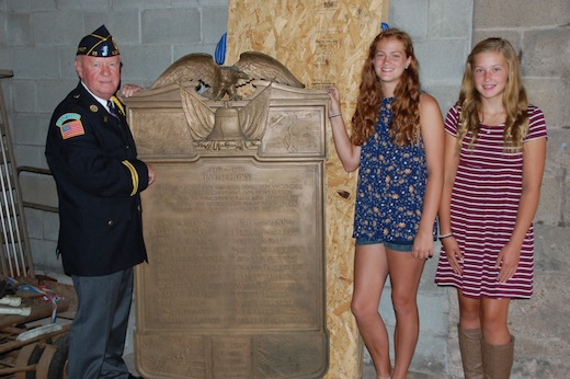 Provided photo: American Legion Sheret Post #35 Commander Wally Skrypnik is pictured with a large bronze plaque memorializing 24 area soldiers who died during World War I. Skrypnik is pictured with Albion seventh graders Leah Pritchard, center, and Emily Harling. The seventh grade service learning class is working on having the memorial placed at Mount Albion Cemetery.