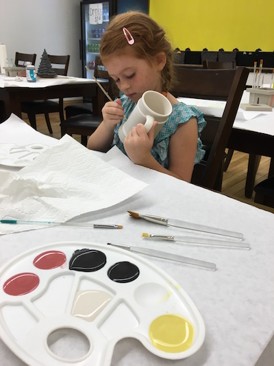 Madelyn Elliott, 7, works on a ceramic at her parents' business on Saturday.