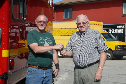 Provided photo: Chris Chilson (left), Fancher-Hulberton-Murray Fire Chief, hands the keys to a truck to Laverne Bates, executive director of the Genesee-Orleans Ministry of Concern. They are pictured by a low mileage truck in red that was purchased by GOMOC from FHM. The previous truck in yellow needed costly repairs.