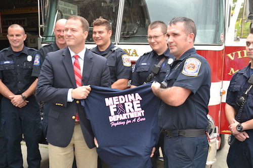 State Sen. Robert Ortt and Medina firefighter Steve Miller hold a T-shirt the Fire Department is selling to raise funds for breast cancer awareness and research. Those shirts are available throughout the year at the Fire Department.