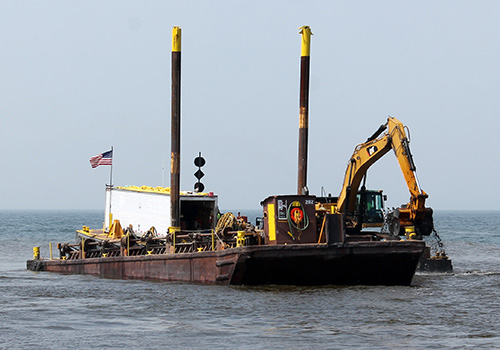 File photo: The dredging barge is near the breakwall at the Oak Orchard Harbor in this photo from August 2014.