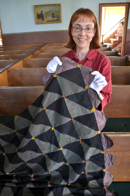 Sue Bonafini holds one of the antique quilts that will be part of a show on Sunday at the Cobblestone Museum.