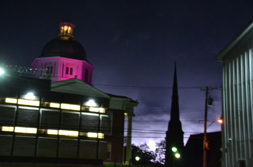 File photo by Tom Rivers: The Orleans County Courthouse has a pink tint in honor of Breast Cancer Awareness Month in this photo from last October. The photo also shows the Orleans County Jail and the Presbyterian Church. The dome will shine green for the first time on March 12.