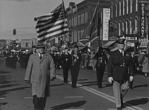 The parade, led by Gen. John S. Thompson as parade marshal and the Sheret Post Legion Band, escorts the men of Company F along Main Street in Medina as they approach the rail station. Many of these men bade farewell to Orleans County boys in a similar fashion to their own departure for the First World War just 23 years earlier.