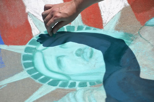Photos by Tom Rivers:Jennifer Gray, a chalk artist and director of the Genesee-Orleans Regional Arts Council, works on a chalk art creation of the Statue of Liberty and an American flag on May 27 by the Albion Middle School. The Arts Council requested a funding boost from the county from $3,000 to $5,500. The tentative budget keeps the funding at $3,000.