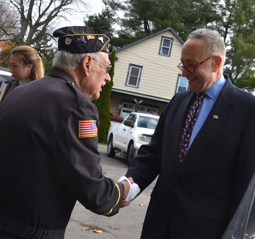 U.S. Sen. Charles Schumer shakes hands with Chipper Gifaldi, a World War II veterans, today before a Veterans' Day program at the American Legion in Holley.
