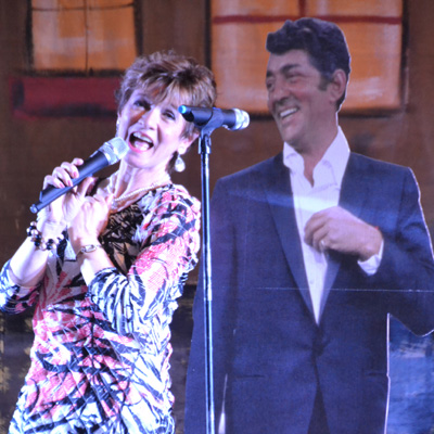 "File photos by Tom Rivers: Marcy Downey sings ""Baby, It's Cold Outside"" next to a cutout of Dean Martin during last year's Hometown Christmas."