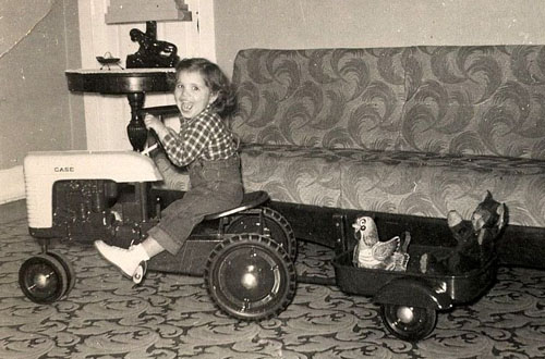 """The book includes many pictures of """"farm kids,"""" including this one of Holly Ricci as a girl on a pedal tractor."""