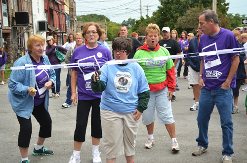 "Nicole Tuohey cuts a chain with ""elephant links"" representing donations to fight Alzheimer's Disease. Tuohey typically raises about $1,000 each year for the ""Walk to End Alzheimer's."""