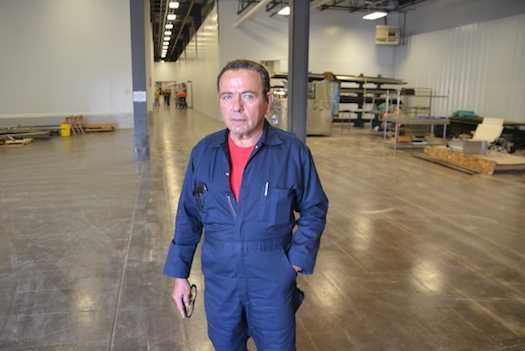 Steve Karr, the Pride Pak CEO, is pictured in overalls in mid-October when he was working with contractors helping to measure and connect lines that day. He is pictured in the warehouse space, which was the scene for an upscale party on Wednesday.