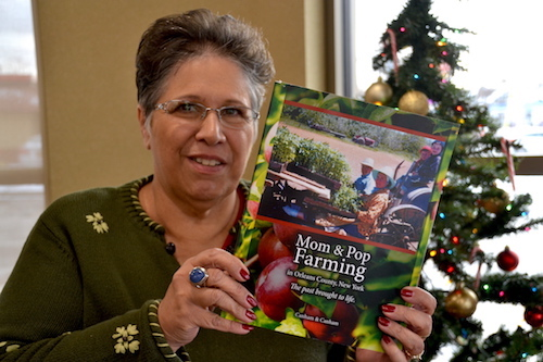 "Holly Ricci-Canham holds a copy of ""Mom & Pop Farming in Orleans County, New York – The past brought to life."" She worked two years on the 300-page book, interviewing 150 farmers."