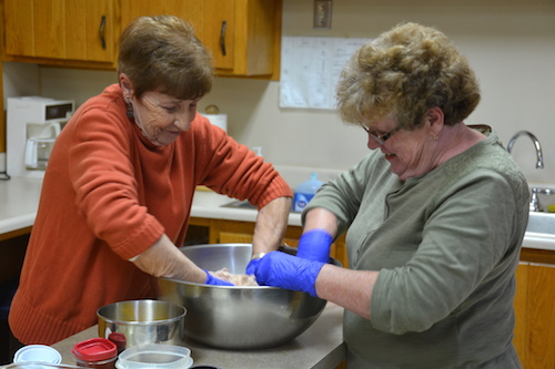 Mary Ellen Seaman and Kathy Scroger work together on making the Hardenbrook family ham loaf at the Morton Baptist Church.