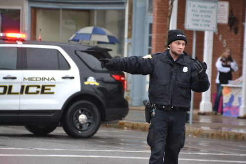 Photo by Tom Rivers: Medina Police Officer Corey Ambrose directs traffic last month during the Olde Tyme Christmas celebration. Medina, Albion and Holley village police departments. Lyndonville also has an officer.