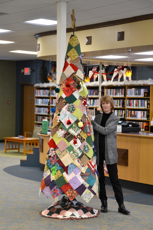 Photo by Tom Rivers: Catherine Cooper, director of Lee-Whedon Memorial Library in Medina, stands next to a tree created with 300 quilt squares.