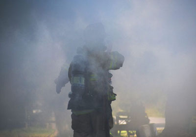 File photo by Tom Rivers: Two firefighters battle smoke at a fire on Phipps Road in Albion on Sept. 19, 2014.