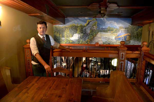 Tony McMurtrie is pictured in the mezzanine with a Erie Canal mural created by Stacey Kirby.