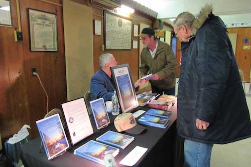 """Tom Totter speaks with Michael Keene during the book signing. Totter said his wife is the niece of Ronald Sisson, one ofthe Holley Boys. She was, """"very moved by the book,"""" Totter said."""