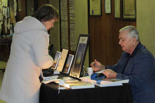 """Photos by Kristina Gabalski: Author Michael Keene signs a copy of his book: Vietnam Reflections: The Untold Story of the Holley Boysfor Bev Brennan, a Holley native who lives inBrockport. Brennan said she graduated from Holley prior to the Holley Boys, but has siblings their age. Keene did, """"an excellent job,"""" with the book,Brennan said."""