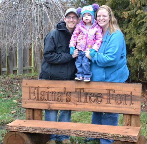 """Kyle and Beth Webb snuggle with their daughter Elaina at """"Elaina's Tree Fort."""""""