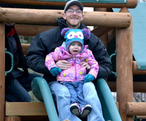 Elaina Webb is thrilled to head down the slide with her father, Kyle.