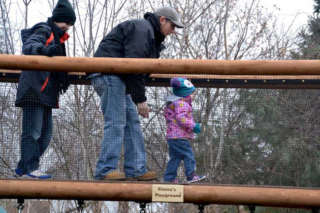 Elaina Webb, 2 ½, is shown with her father Kyle Webb and older brother Colin after a new playground was opened at about 4 p.m. today in the family's backyard on Herrick Street in Albion.