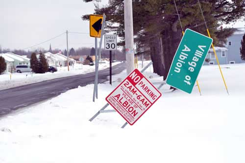 File photo: A smashed sign shown in the winter of 2014 in the village of Albion is symbolic of the rough roads villages are charting due to miniscule aid from the state. Cities get far more in per capita funding than villages.