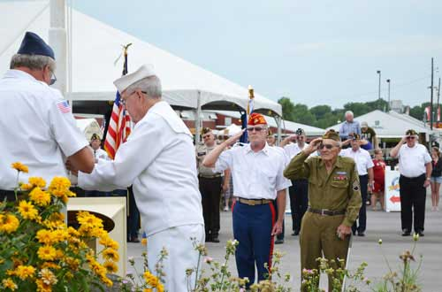 World War II veteran Michael Paduchak, right, and George Blakeman, a member of the Marine Corps League in Albion, salute during the flag-raising ceremony in July 2013 to kick off the Orleans County 4-H Fair.