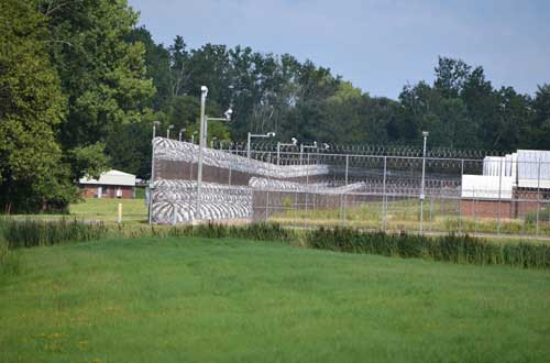 The Orleans Correctional Facility is lined with a razor-wire fence. The facility was built on Gaines Basin Road about three decades ago.